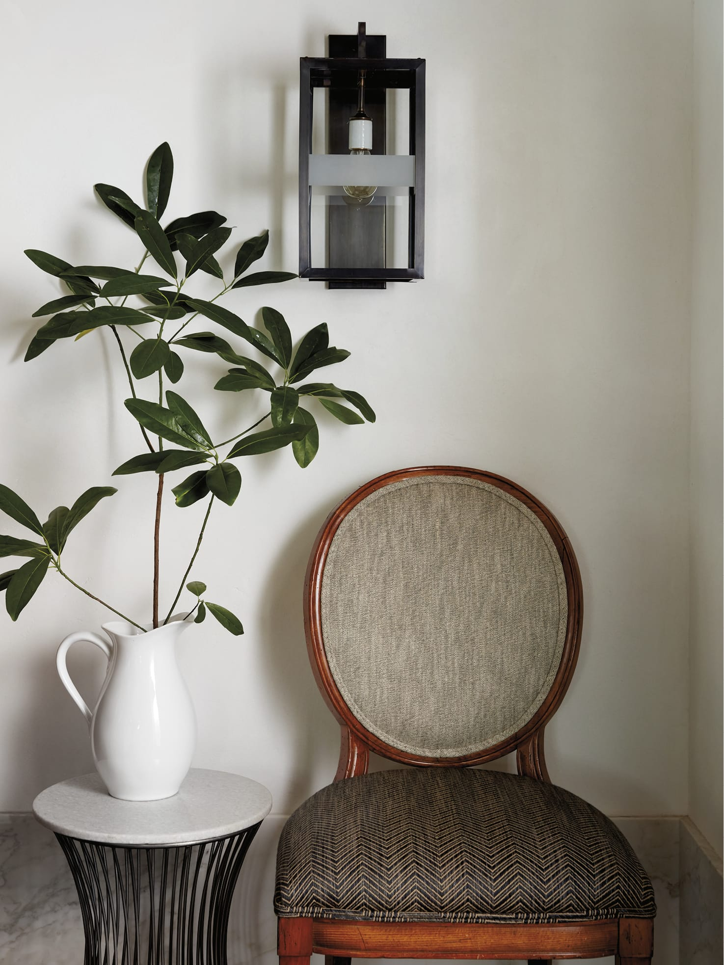 Chair next to plant in vase