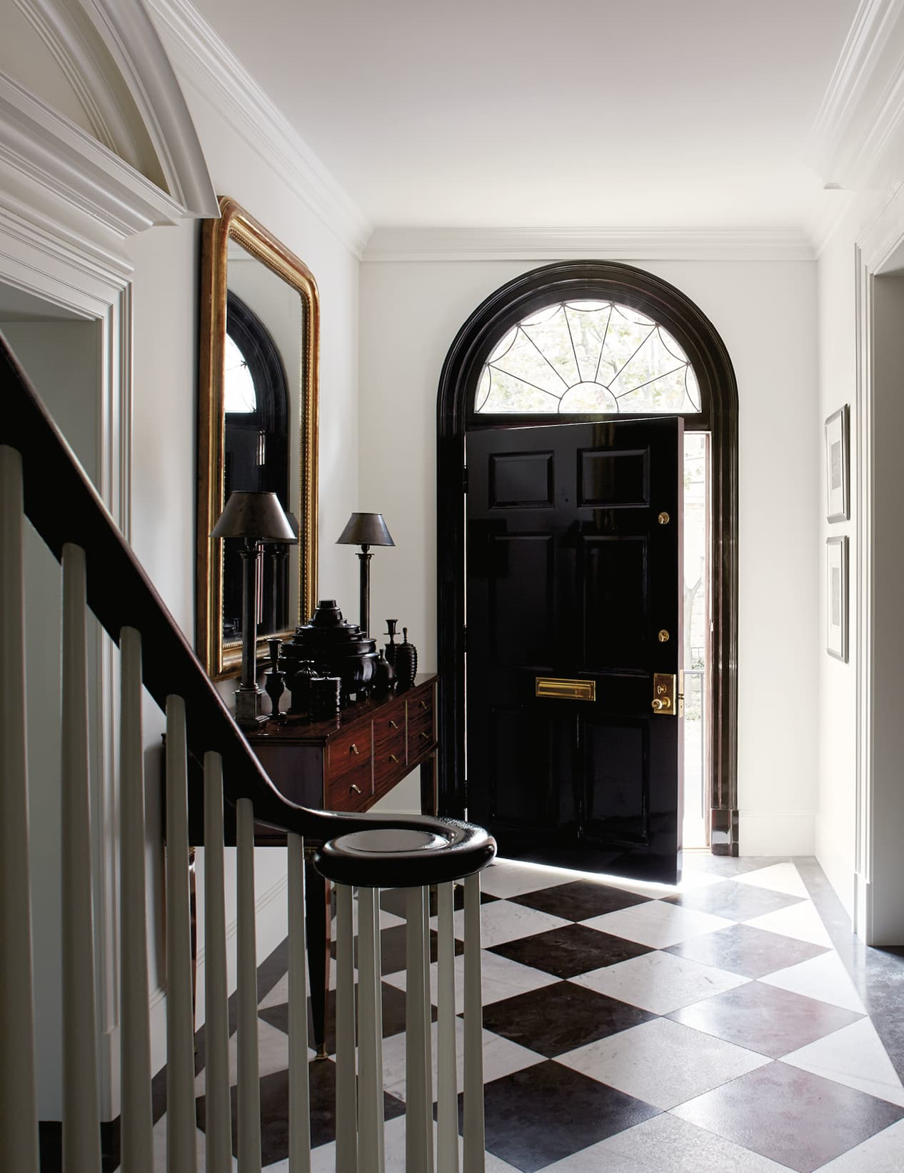 Foyer with black and white tile floor and a black door