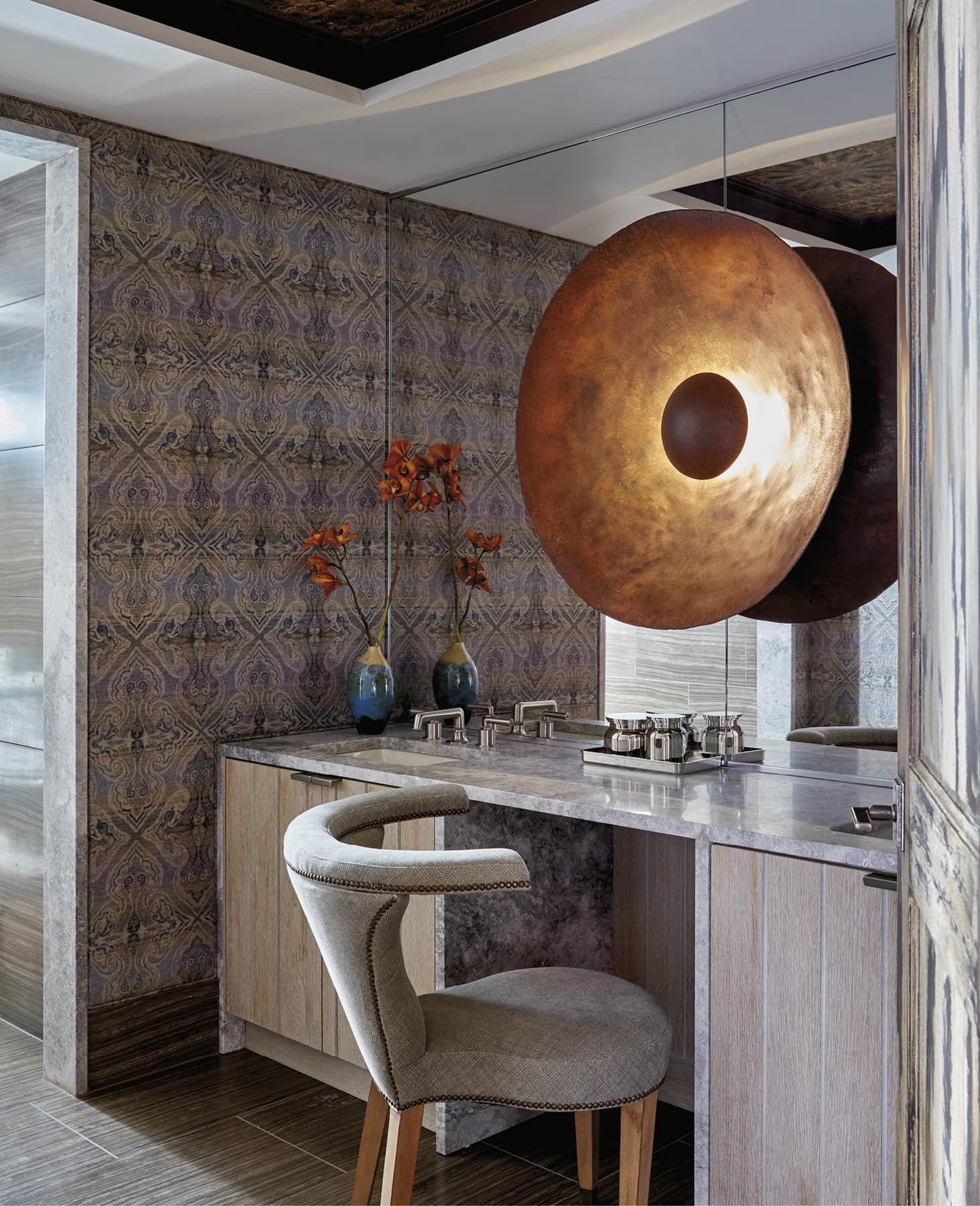 Bathroom vanity with a large decorative light on the mirror