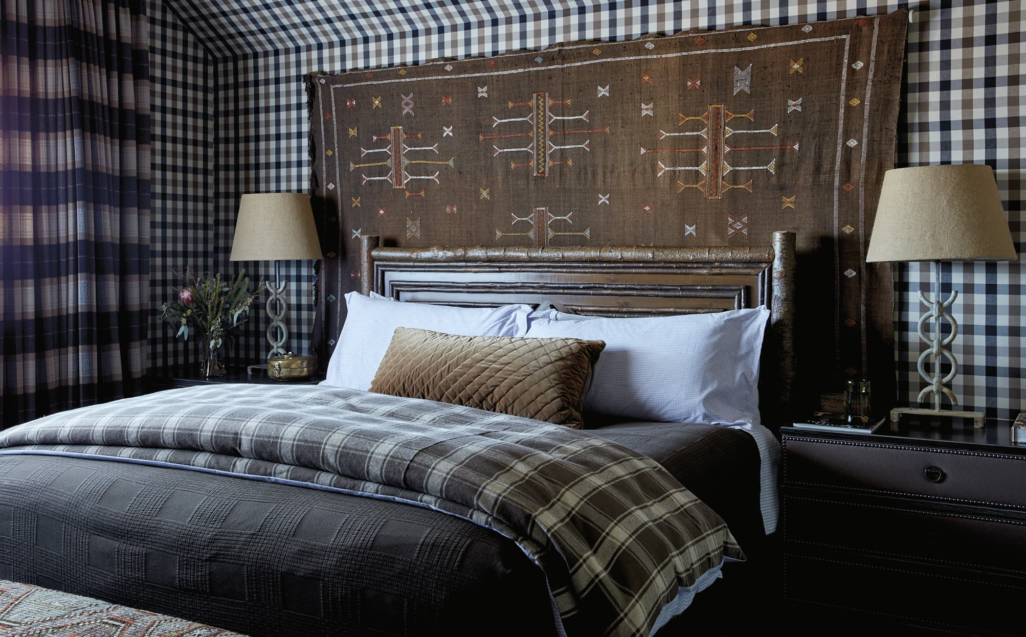 Bedroom with a large tapestry and plaid walls