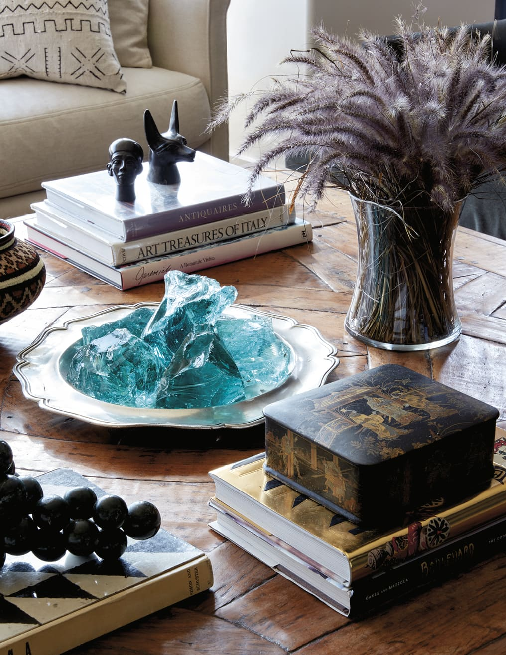 Closeup of items on a coffee table, including a plate of blue stones