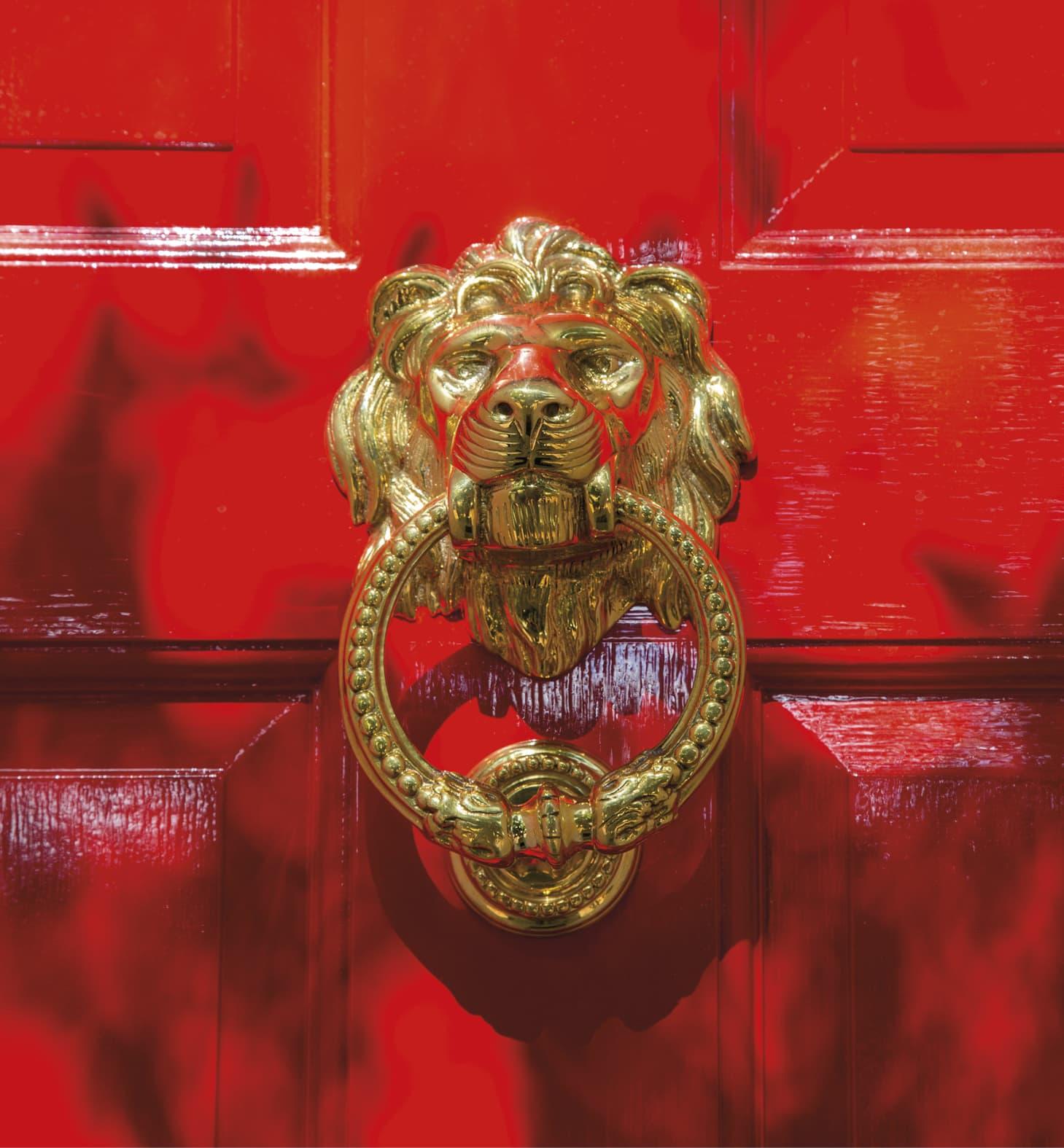 Closeup of a lion's head knocker on a red door