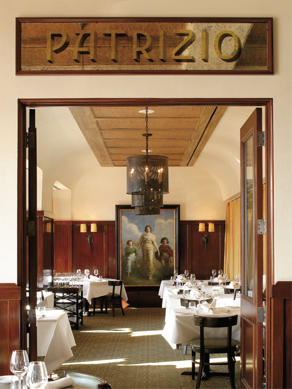 Looking through a door into the dining area with a painting hanging on the wall