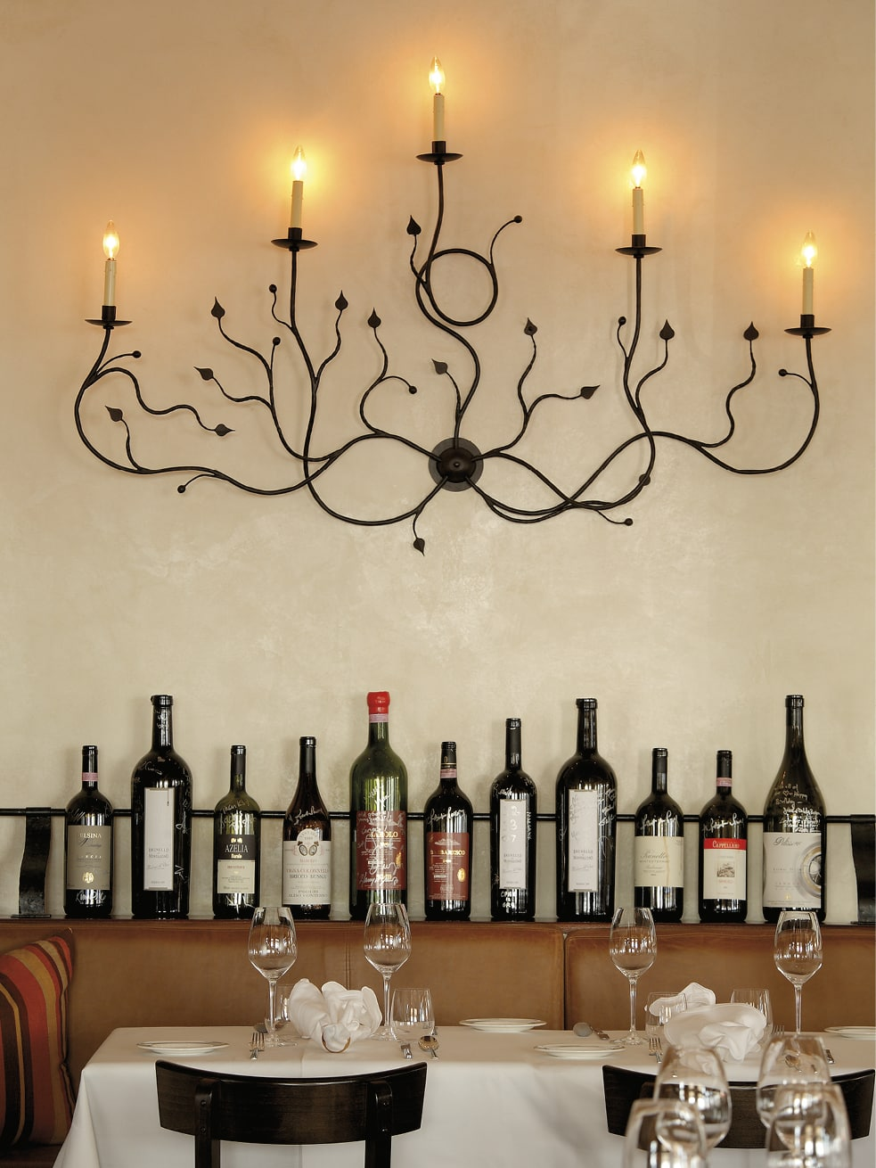 An elaborate wall sconce with wine bottles underneath