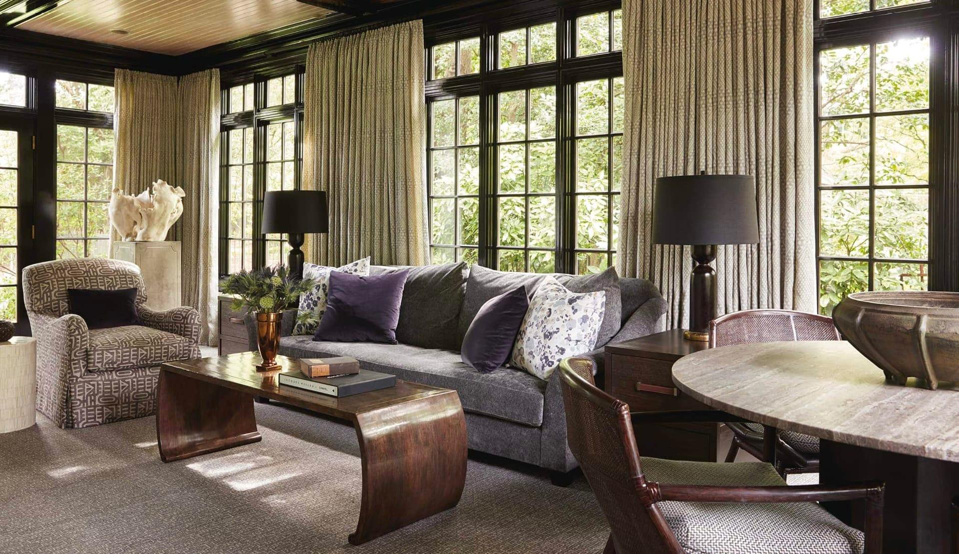Sunny siting area with dark wood trim and comfortable sofa and chairs